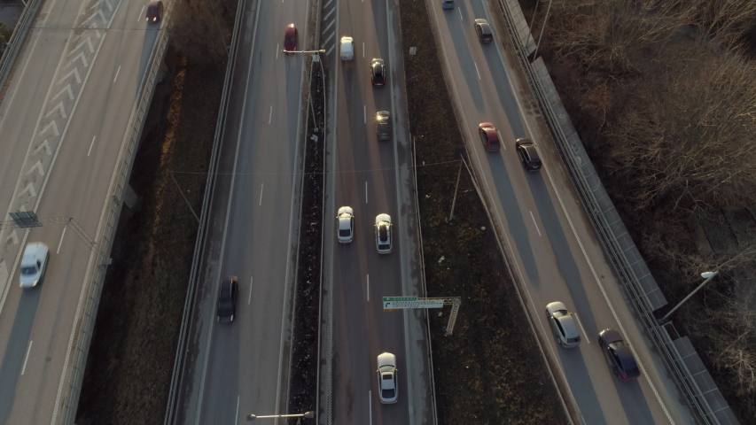Aerial view of elevated highway traffic at sunset. Drone shot flying over junction, rush hour cars driving by. Urban transportation and air pollution background in 4K resolution Royalty-Free Stock Footage #1053786065