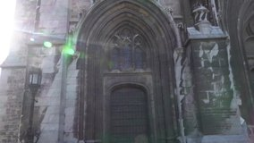 Facade of the old Catholic Gothic Church. Video with the effect of glare on the lens.