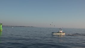 Small fishing boat returning to harborwith lots of seagulls. Slow motion video.