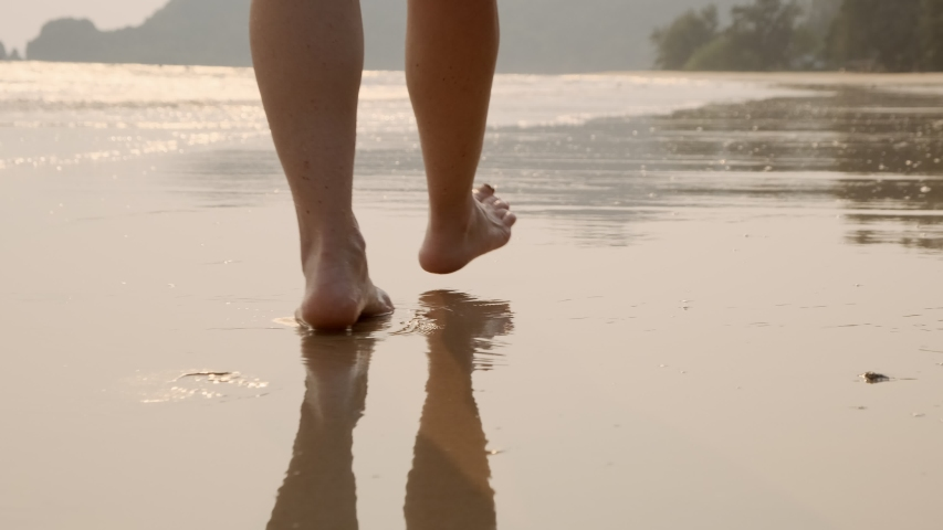 Woman feet walking barefoot on sandy beach of sea. Royalty-Free Stock Footage #1053796130
