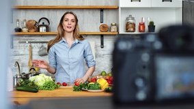 Adorable woman talking recording cooking video at kitchen interior. Beautiful young female blogger preparing healthy food use fresh organic vegetable. Shot on RED Raven 4k Cinema Camera