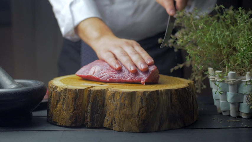 A man cutting beef meat and bones into small pieces on a wooden chopping board with clean environment.