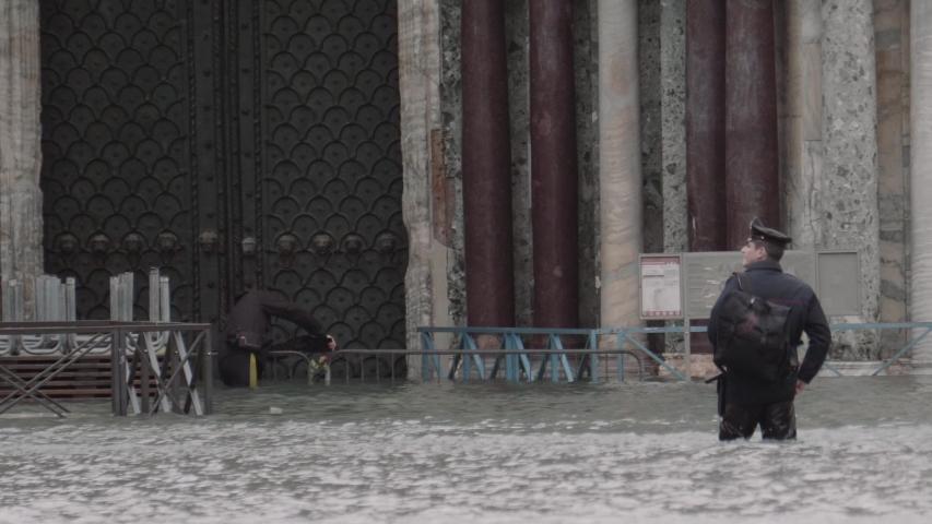 VENICE, ITALY - CIRCA NOVEMBER 2019: Policemen surveilling the entrance of a church during the flood in Venice.