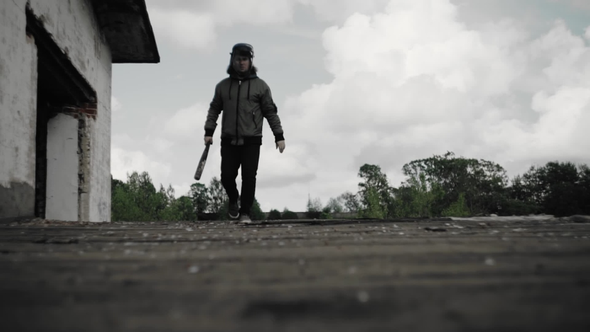 A man with a baseball bat walks on the roof of an abandoned house. He looks around. General plan. Disobedience and disorder