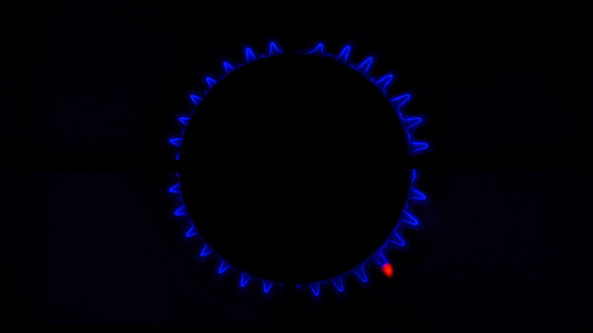 Kitchen burner turning on Stove top burner igniting into a blue cooking flame Natural gas inflammation Close up Cook sets fire to the stove burner turning on Stove top View - Shot burner igniting
