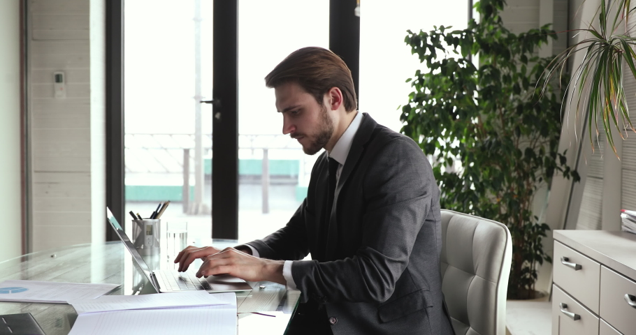 Serious concerned young businessman wears suit doing financial market research working online on laptop. Busy smart ceo thinking of strategy plan managing risks, solving business problem use computer. Royalty-Free Stock Footage #1053810374