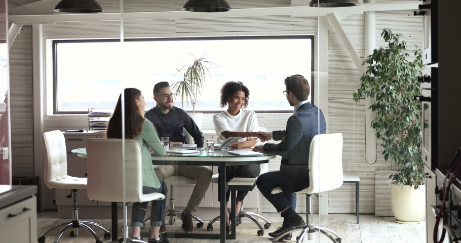 Happy diverse colleagues or partners handshaking negotiating in modern board room behind glass at multiracial group meeting expressing partnership and teamwork professional collaboration concept. Royalty-Free Stock Footage #1053812690