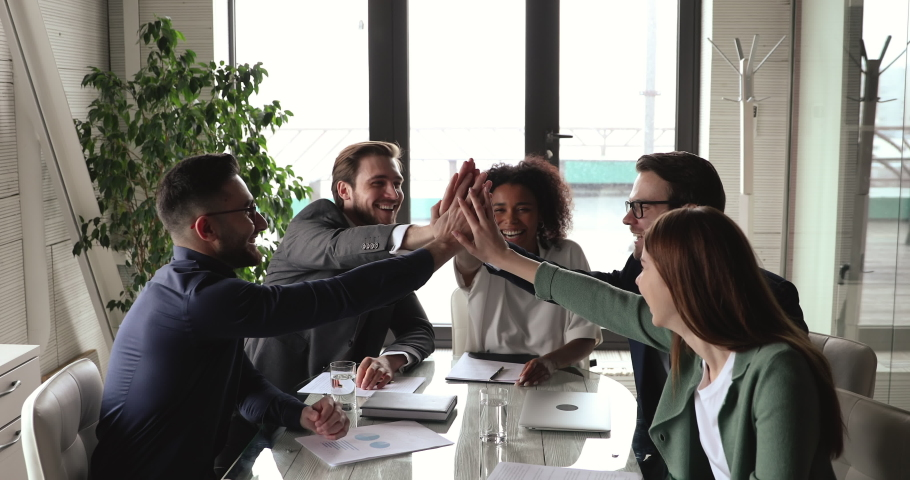 Happy multiethnic professional business team give high five together sit at office meeting table. Diverse executives group celebrate corporate success engaged in teamwork trust partnership concept. Royalty-Free Stock Footage #1053819998