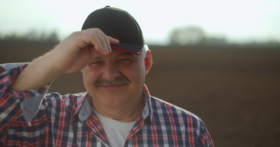 A tractor driver after plowing looks at the camera after a working day at sunset | Shutterstock HD Video #1053820058