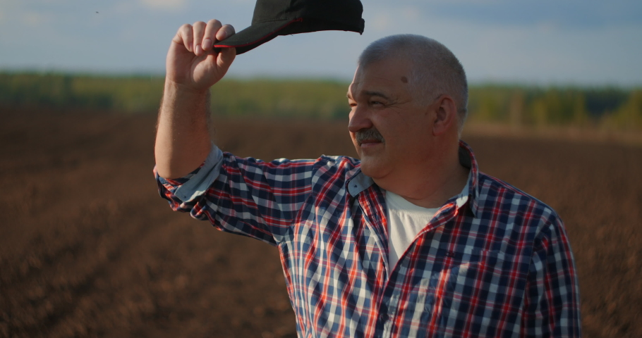 A male farmer takes off his baseball cap and looks at the sunset after a working day. a farmer looks at the sunset in a plowed field | Shutterstock HD Video #1053820148