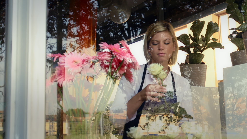 Businesswoman in her own flower shop, preparing bouquet of flowers and holding roses. Pretty girl self-employed in florist store. Confident young woman at work in Milan. Dolly shot
