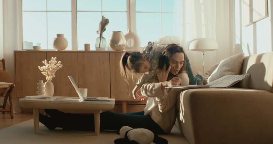 Mother working from home, having a phone call, while her daughter distracts her and drawing attention. Shot on RED Dragon | Shutterstock HD Video #1053824999