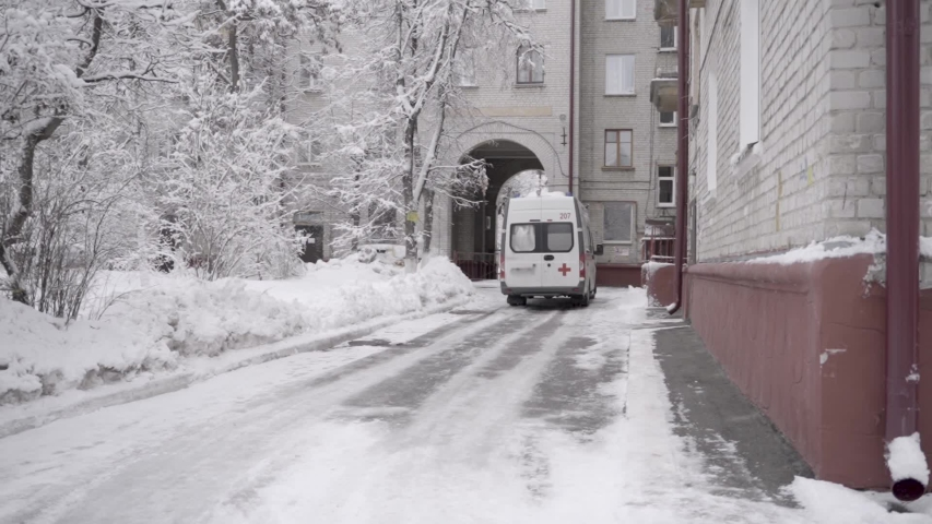Ambulance car pulls up and stops in the snowy winter before the entrance of the house. | Shutterstock HD Video #1053828416