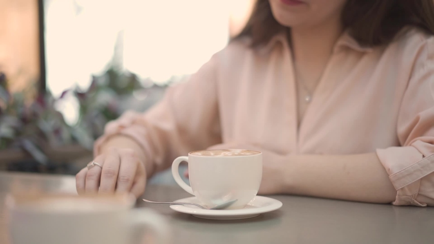 Closeup female hands pour sugar from a bag into a cup with coffee. a woman in a cafe in a sales center pours sugar into a cup of cappuccino. | Shutterstock HD Video #1053828422