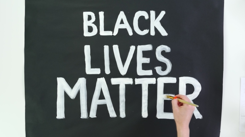 timelapse. close-up, hand writes slogan - Black Lives Matter - with brush, using white paint on black banner, poster. Fighting against racism, for equal rights in USA. Royalty-Free Stock Footage #1053836849