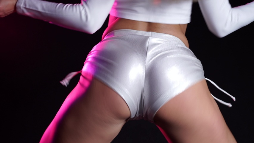 Sexy woman in short silver shorts dancing modern dance - twerk. Girl shaking, twerking her buttocks close up on black background, neon light. | Shutterstock HD Video #1053848162