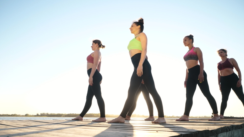 Fitness Class of Diverse Five Happy Women Group Doing Stretching Position, Warm Up Together Standing on Boardwalk in Sunshine Outdoors. Exercising Healthy Lifestyle, Body Care for Wellness, Calm Relax