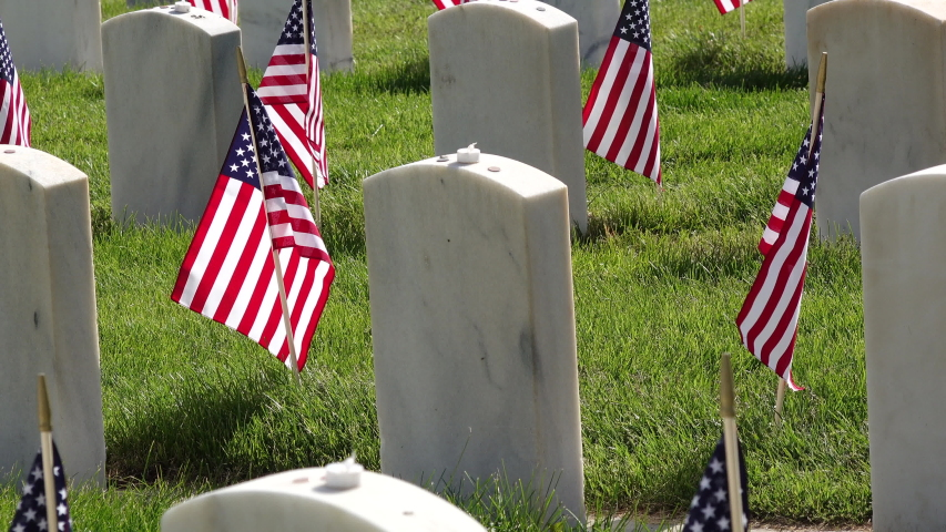 American Flags adorning military headstones at cemetery for Memorial Day