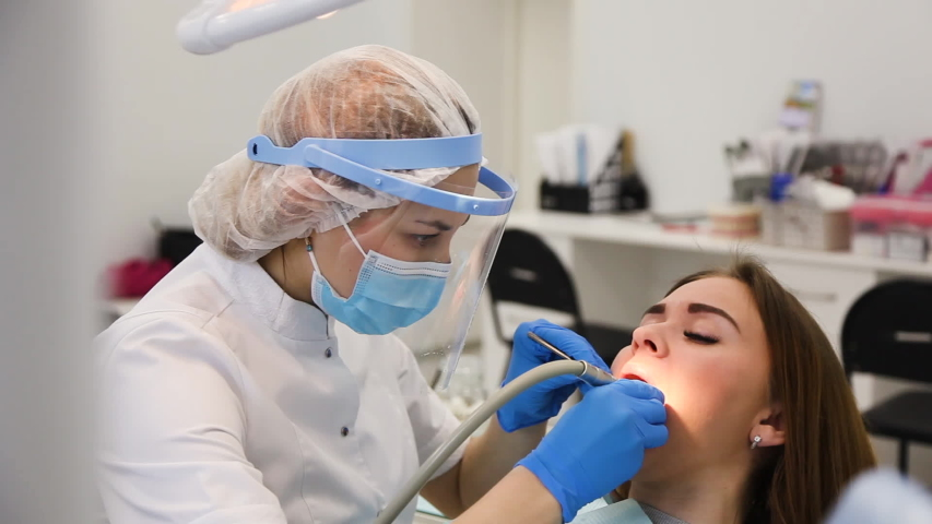 Young female dentist curing tooth cavity. Patient with caries on chair. Stomatologist and patient at clinical office. Toothcare concept Royalty-Free Stock Footage #1053852923