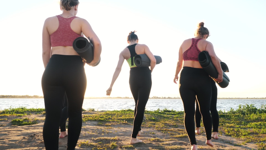 Back View at Diverse Group of Five Young Adult Talking Women Holding Sport Mats in Hands Going on Fun Fitness Training Together Ready to Workout Outdoors Near Lake. Healthy Body Lifestyle for Wellness
