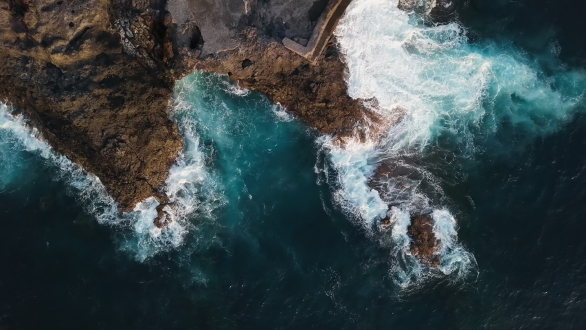 Top aerial view of ocean waves splash against rocks background, Tenerife, Canary islands, Spain.