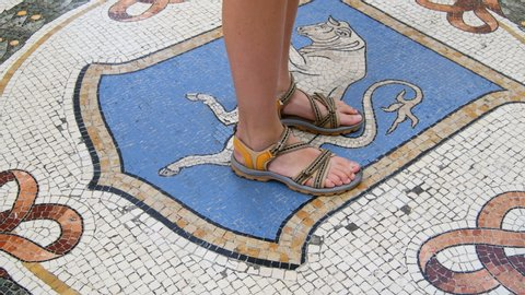 Tourist doing turns with the heel on the mosaic bull balls on the floor - Vittorio Emanuele gallery of Milan in the north of Italy - legend about bringing luck - Real Time in 4K