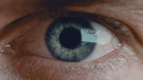 Close up shot of eye opening with beautiful blue iris. Healthy eyesight concept. Front view macro video in 4K.
