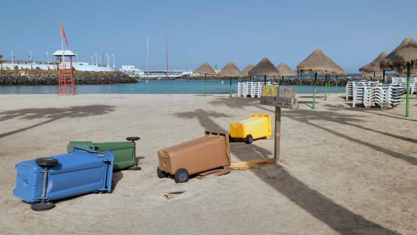 Trash cubes lying on the sand at an empty tourist beach locked due Covid-19 pandemic. Playa de La Pinta, Tenerife (Canary Islands)