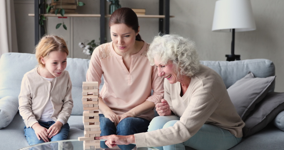 Excited little 6 or 7 years old cute redhead child involved in funny build board game with smiling young mother and happy senior older granny, building wooden tower and taking out blocks at home. Royalty-Free Stock Footage #1053902228