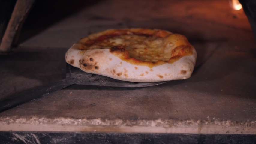 Restaurant chef takes out cooked thick pizza with baked golden cheese crust of stone oven extreme close view | Shutterstock HD Video #1053902342