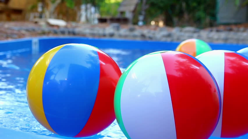 Colorful beach balls floating in pool.