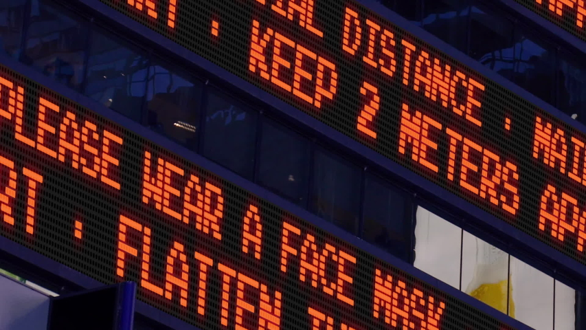 Closeup view of a news ticker reminding pedestrians to keep 2 meters apart from each other. Social distancing was a common practice to slow the spread of COVID-19 during the pandemic of 2020.  	 Royalty-Free Stock Footage #1053913475