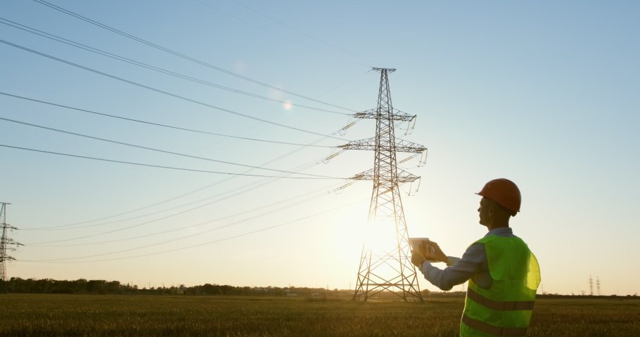 An energy engineer in special clothes inspects a power line using data from electric sensors on a tablet.