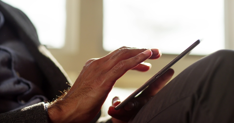 4k businessman using a touchscreen tablet computer surface while internet surfing. Royalty-Free Stock Footage #1053922121