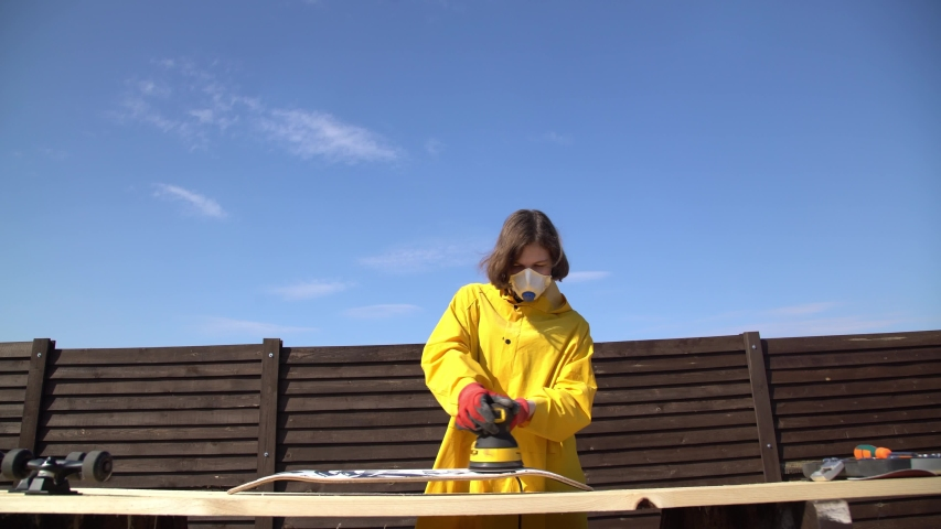 Young girl making skateboard. Skateboarding Woodworking. Grind wood. DIY. Yellow raincoat. | Shutterstock HD Video #1053924776