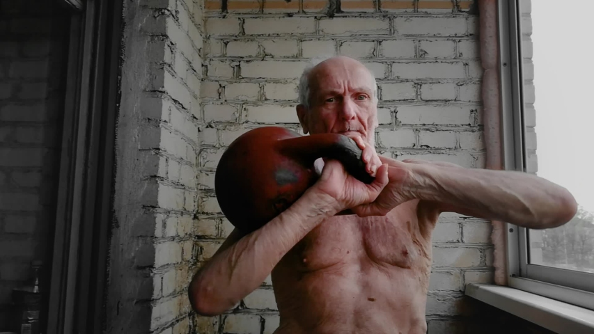 Man 80s 90s years old lifts dumbbell kettlebell up. Workout by gaffer oldster retiree inside balcony of the apartment at home. Sports and fitness. Healthy life. Morning exercise for caucasian man | Shutterstock HD Video #1053928868