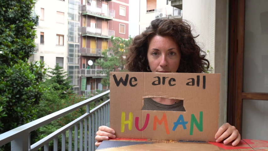 America USA - white latin girl holding sign we are all human  protest and manifest - racism and social violence Royalty-Free Stock Footage #1053930851
