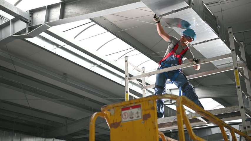 Caucasian Male Worker Inspecting Hvac Air Duct System Installed On Ceiling Inside Of New Construction Site. | Shutterstock HD Video #1053936848