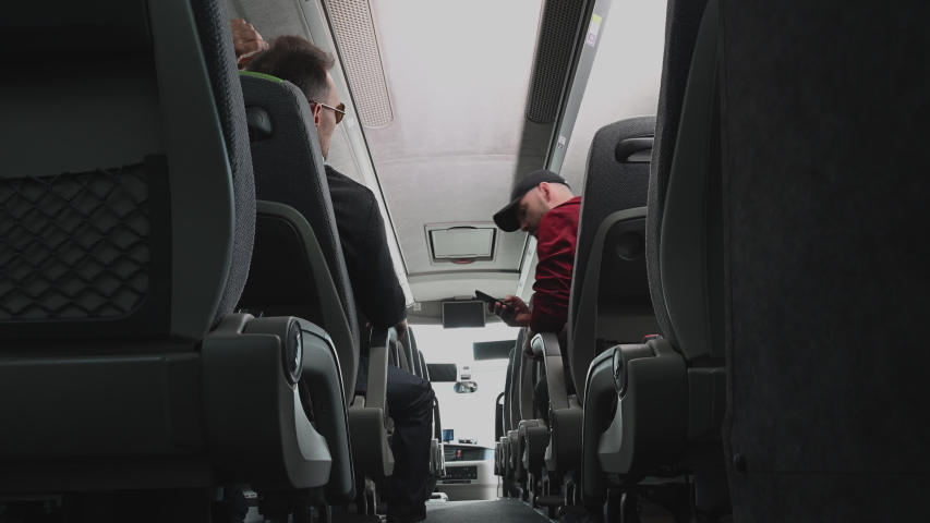 Male Passengers Sitting On Bus Talking To Each Other Adjusting Seats And Checking Cell Phone. | Shutterstock HD Video #1053936917