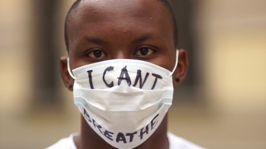 Outdoor portrait of a African American in a medical mask with the inscription I cant breathe. Black lives matter, mass protests against racism in the USA and Europe
