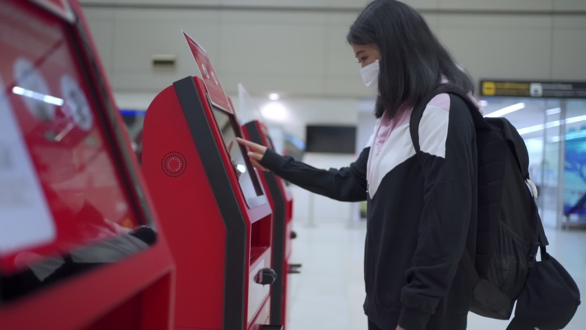 Asian woman travel in protective mask using ticket kiosk machine, self check-in at airport terminal, online ticket booking travel, virus covid-19 pandemic, new normal social distance, slow motion