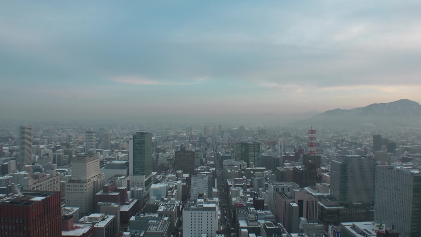 SAPPORO, HOKKAIDO, JAPAN - FEB 2020 : Aerial high angle sunset view of cityscape of Sapporo city. View of buildings and street traffic around Susukino downtown area. Time lapse shot sunset to night.