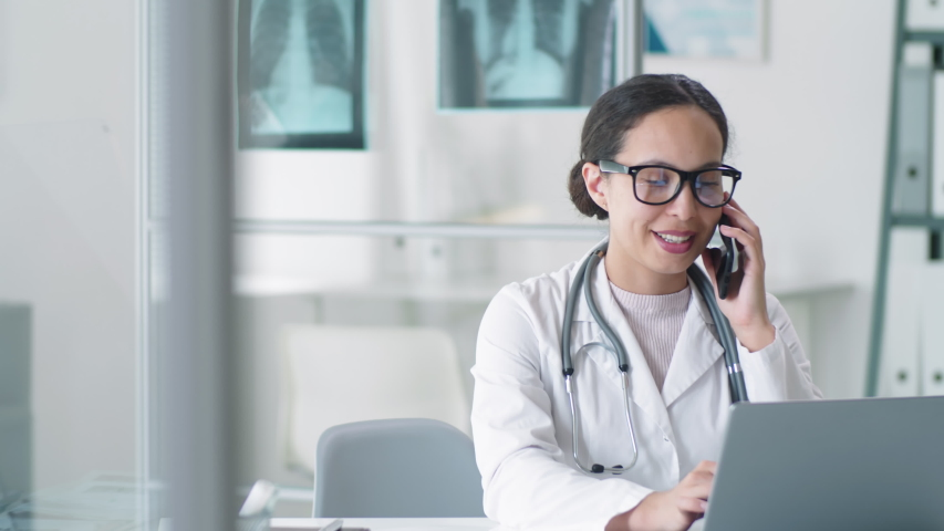 Young mixed-raced female doctor in lab coat, glasses and stethoscope over her neck using laptop, smiling and speaking on mobile phone at desk during workday in clinic Royalty-Free Stock Footage #1053953228
