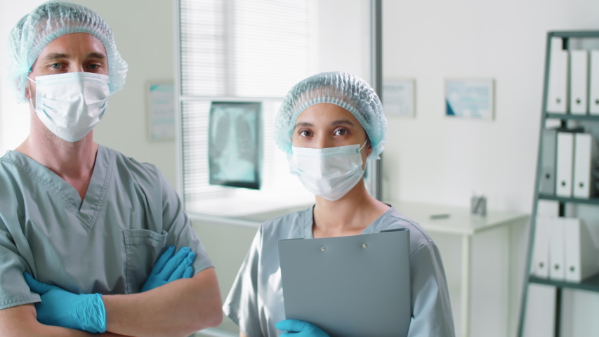 Professional male and female doctors in protective masks, disposable hats and gloves posing together for camera in hospital during coronavirus outbreak Royalty-Free Stock Footage #1053955169