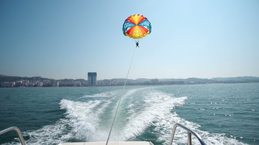 Excited tourists parasailing high in the sky, extreme sport, summer activities.