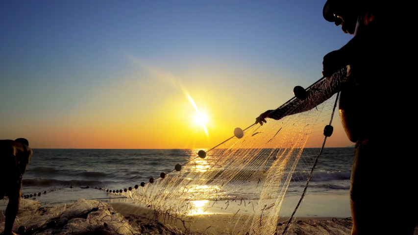 Fishermen fishing in the early morning golden light manual hand pulling the net