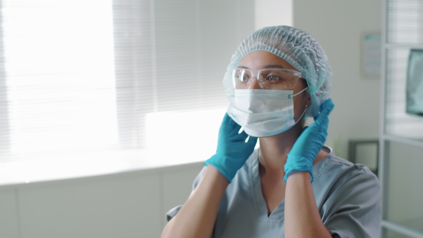 Young female nurse and professional male doctor in protective uniform, glasses, hats and gloves putting on medical masks and walking away while working in hospital during coronavirus pandemic Royalty-Free Stock Footage #1053956054