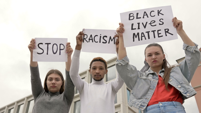 Three young people of different nationalities protest against racial inequality. They have posters in their hands STOP RACISM and BLACK LIVES MATTER.