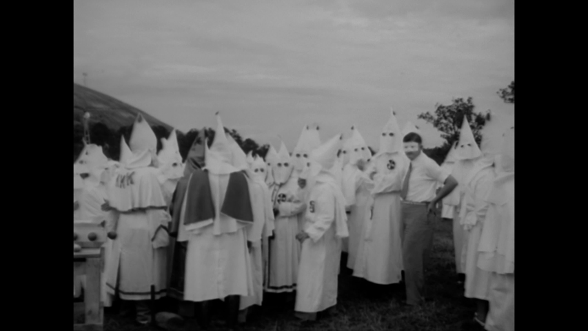 CIRCA 1949 - A child is held up at a Ku Klux Klan rally in Stone Mountain, Georgia, and new members are initiated in a cross burning ceremony.