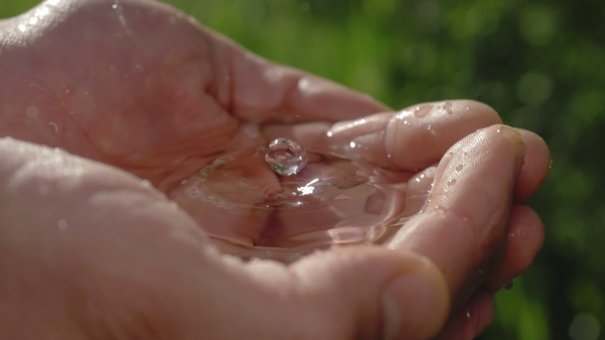 clean water in human hands. stream of pure water pouring into male hands. water drops, water resources, earth, environment. conservation of natural resources. Royalty-Free Stock Footage #1053960956